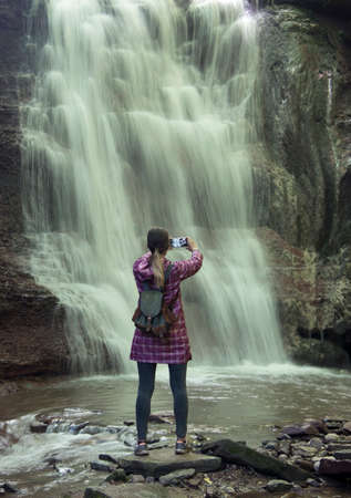 The girl in a bright raincoat phone photographs a waterfall. Фото со стока