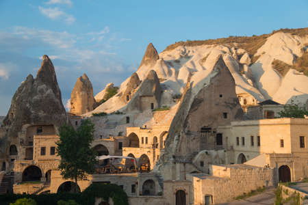 Dwellings in the cliffs of Cappadocia. Blue sky with clouds in background.