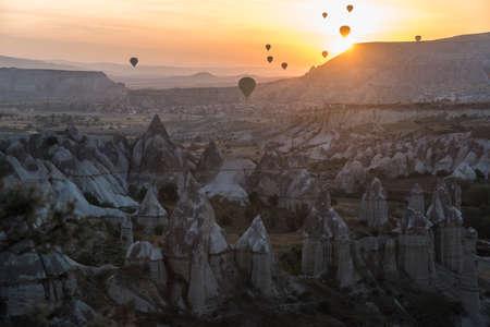 Hot-air balloons against sunrise scene. Cappadocia. Famous Cappadocia rocks in foreground. Редакционное