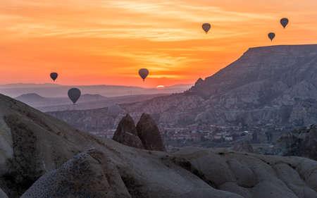 Hot-air balloons silhouettes against sunrise scene. Cappadocia. Little sun is seen over horizon.