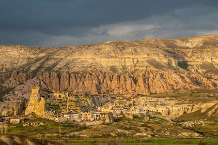 Cappadocia - buildings in rocks and natural mountains on back plan. Cavusin (Chavushin) village. Редакционное