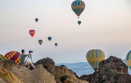 Photographer with a tripod photographs balloons in Cappadocia. Редакционное