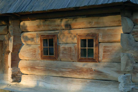 Wooden house with two windows close up. Stock Photo