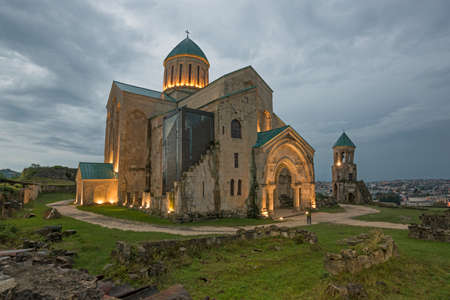 Illuminated Bagrati Cathedral against gray sky background.  Another church names: Cathedral of  Dormition or  Kutaisi Cathedral.