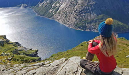 Girl in a hat contemplates beautiful fjord in Norway.  Lake and hat are blue. Girl is dressed in red sleeve t-shirt.