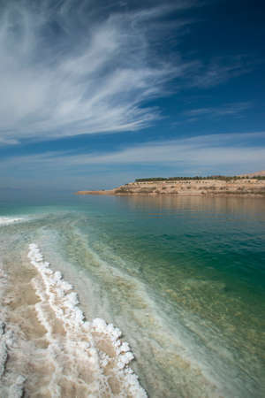 Salt pattern on Dead Sea coastline. Cirrus clouds in blue sky complement the composition well.
