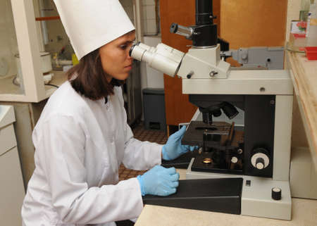 Woman in a white coat, hat and gloves uses a sampler to apply a sample to a glass slide. Medical laboratory  scene. Stock Photo - 161687505