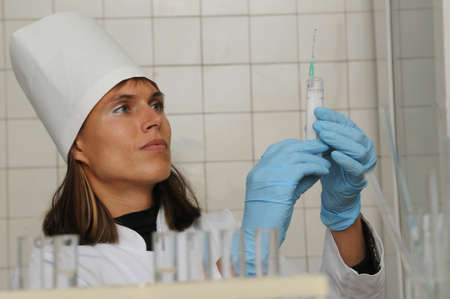 Woman in a white coat, hat and gloves uses a sampler to apply a sample to a glass slide. Medical laboratory  scene.