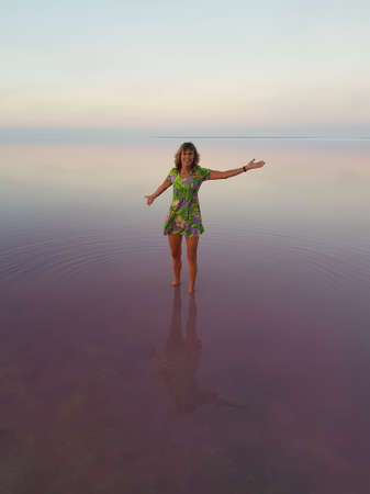Happy woman in bright dress in the middle of pink lake. Water is perfectly smooth.