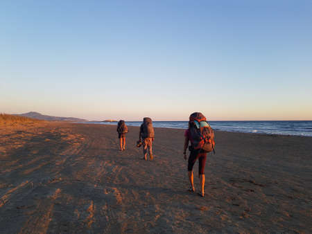 Tourists with backpacks walk along Patara beach. The beach is lit up with evening light.