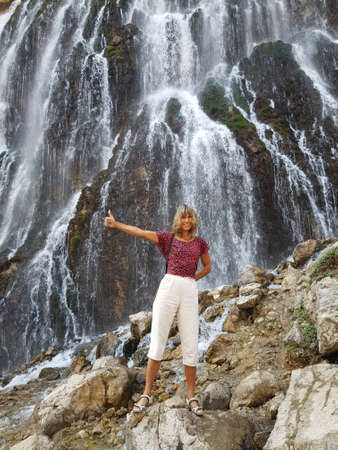 Happy girl in front of a massive Kapuzbasi waterfall.