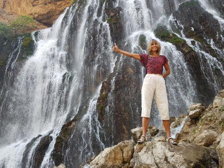 Smiling girl in front of massive Kapuzbasi waterfall.
