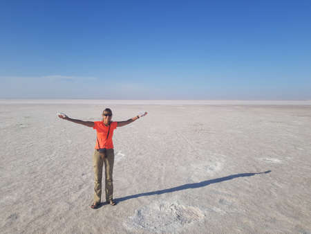 Girl in bright clothes with outstretched arms in the middle of salt desert. This is the bottom of dried Tuz lake. In the girl's hand, collected healing salt.