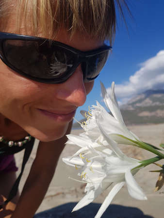 Girl sniffing white Sand lily. Flower is reflected in sunglasses. Blue sky in background. Stock Photo