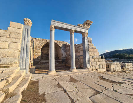 Temple with marble columns in ancient Knidos city. Blue sky in background.