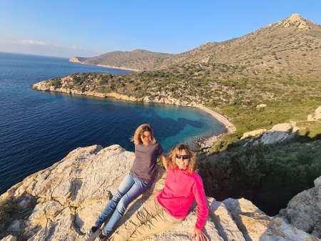 Two womans sit on rock. Seascape of Datca peninsula in background. Stock Photo