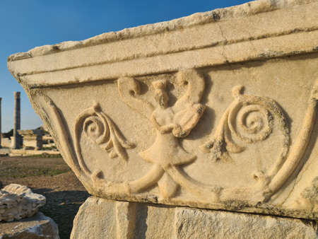 Beautiful pattern is carved into marble part of building. All this is in ancient Knidos. Blue sky in background. Texture of stone is clearly visible.