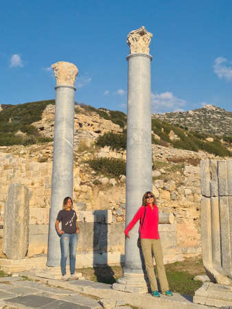 Two girls in ancient Knidos. Young ladies are leaning against marble columns and catching rays of gentle evening sun.