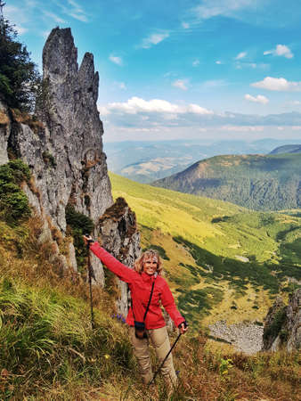 Woman in bright jacket climbs Mount Spitzi. Hiking in Carpathian Mountains.