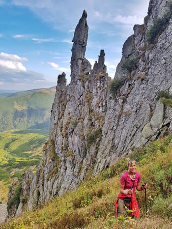 Woman in bright clothes climbs Mount Spitzi. Hiking in Carpathian Mountains.