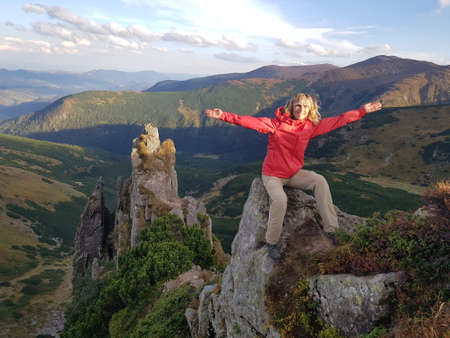 Happy woman posing on Spitzi top. There is beautiful landscape behind tourist. Stock Photo