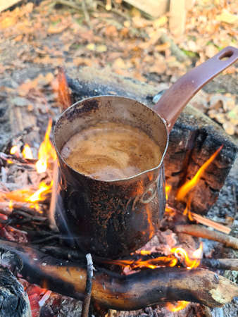 Coffee is prepared in cezve on fire. Vertical image.