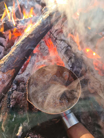 Coffee is prepared in cezve on fire. Vertical composition. Stock Photo