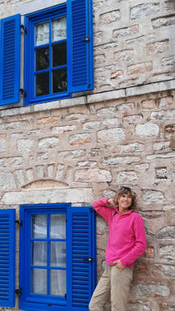 Woman in red polar near stone house with blue windows. Bodrum travel.