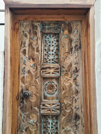 Wooden beautiful old doors in Bodrum. Door is decorated with wood carvings.