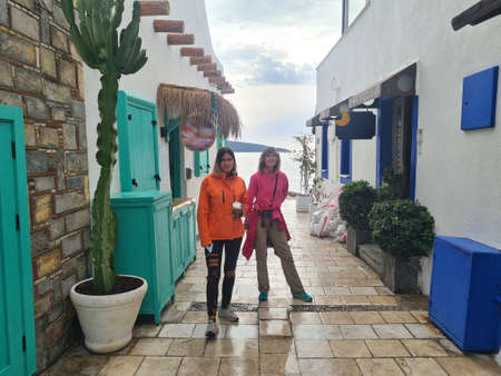 Two women on street with white houses.  Bodrum near embamkment. Stock Photo
