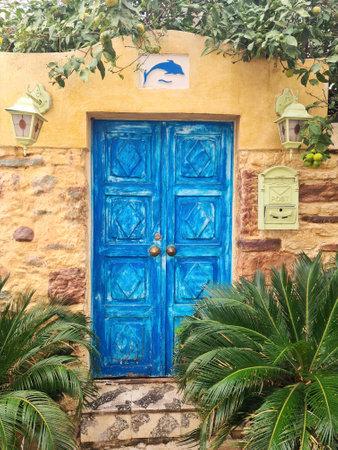 Old blue door in Bodrum. Door is framed by lush green vegetation.