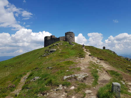 Old observatory on Pip Ivan mountain. Blue sky in background. In some places, on the green slope, pink flowers of Chervona Ruta are visible.