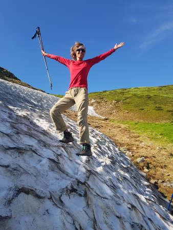 Happy girl in red shirt is standing in snow. Green mountains and a bright blue sky are visible from behind. Stock Photo