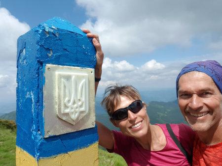 Ukrainian border post in mountains and smiling people next to it. Maramures (Maramuresh) ridge in Carpathian Mountains. Stock Photo