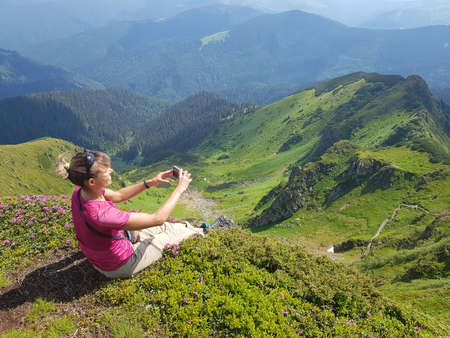 Girl sits in a meadow with pink flowers and takes pictures of mountains by smartphone. Maramures region of Carpathian Mountains.
