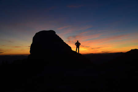 Silhouette of rock and man against morning (sunrise) sky background. Stock Photo
