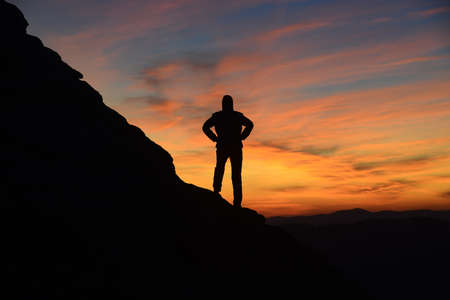 Contemplating sunrise in mountains. Man and mount silhouettes. Stock Photo