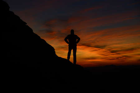 Mount and man silhouette against sunrise background.
