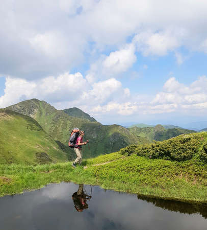 Scene in mountains. Girl with backpack is reflected in mountain lake.