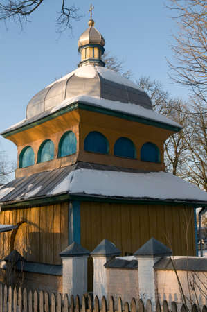 Olyka landmarks. Wooden bell tower of Candlemas (Candlemass, Sretenskaya) church. Church is powdered with snow. Blue sky in background. Stock Photo