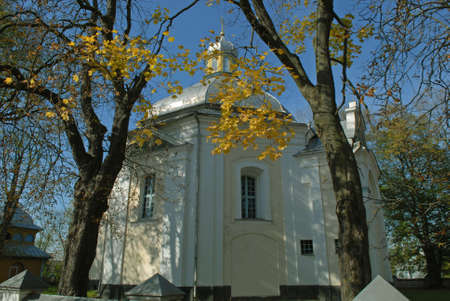 Candlemas (Candlemass, Sretenskaya) church in Olyka. Yellow leaves in foreground. Blue sky in background.