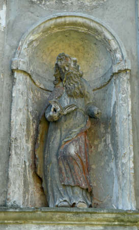 Saint Sculpture on catholic church facade. Colleagues cathedral decoration. Olyka. Stock Photo