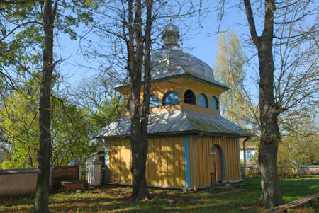 Wooden bell tower among woods. Candlemas (Sretenskaya) church in Olyka. Stock Photo