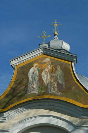 Candlemas (Candlemass) church in Olyka. Painting above entrance: Feast of Jesus Christ Presentation. Blue sky in background. Stock Photo