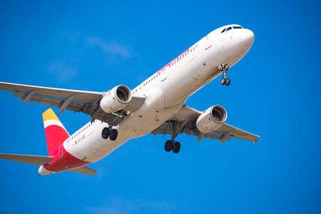 BARCELONA, ESPAÑA - 20 DE AGOSTO DE 2016: Avión de Iberia Airlines que llega al aeropuerto según lo previsto. Aislado en fondo azul. De cerca Foto de archivo - 82332162