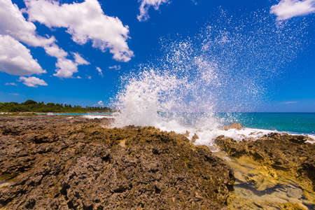 Water splashing - crystal clear sea water beating against the rocks. In Bayahibe, La Altagracia, Dominican Republic. Copy space for text