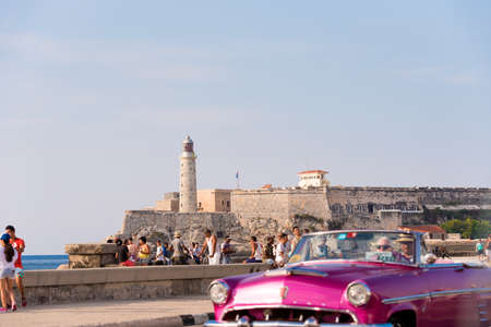 CUBA, HAVANA - MAY 5, 2017: American pink retro-cabriolet on the lighthouse background. Copy space for text