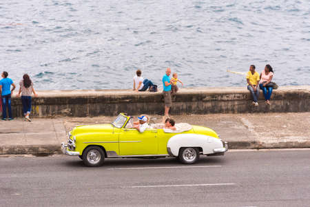 CUBA, HAVANA - MAY 5, 2017: American yellow retro cabriolet rides along the Malecon seafront. Copy space for text Editorial