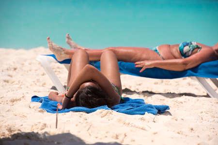 Two women sunbathing on the beach Playa Paradise of the island of Cayo Largo, Cuba