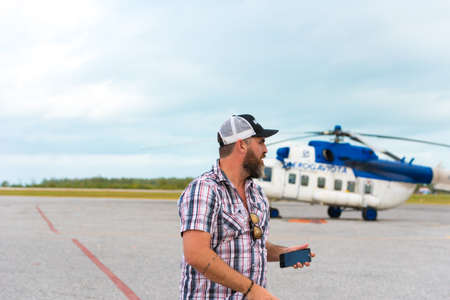 CAYO LARGO, CUBA - MAY 10, 2017: Bearded man in the background of a helicopter at the airport. Copy space for text